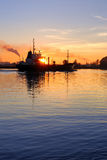 Cargo ship leaving port. At the sunset stock images