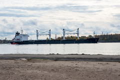 Cargo ship is leaving port sailing away Royalty Free Stock Photography