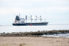Cargo ship is leaving port sailing away Stock Image