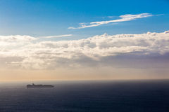 Ship Ocean Destination Sunrise Horizon. Cargo ship loaded with cargo containers heads south with the sunrise from the rear. Photo image overlooking the ocean and Stock Image