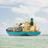 Cargo ship loaded with containers. Blue Cargo ship loaded with containers is leaving the port royalty free stock images