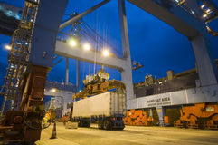 Cargo ship loading containers by night. Royalty Free Stock Image