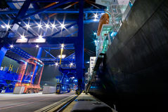 Cargo ship loading containers by night Stock Photo