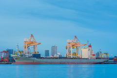 Cargo ship loading containers on schedule. Stock Photos