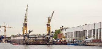 Cargo ship loading cranes in industrial zone on river, freight logistic transportation by water concept. Toned Stock Images