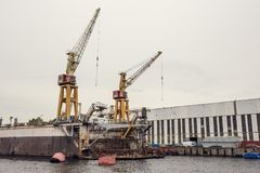 Cargo ship loading cranes in industrial zone on river, freight logistic transportation by water concept. Toned Royalty Free Stock Photos