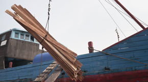 Cargo ship loading goods. Wooden boards are loading in a cargo ship,Jakarta Indonesia Stock Photos