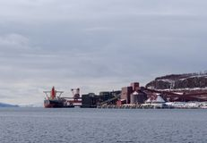 Cargo ship loading iron ore at the Port of Narvik in northern Norway on a winter day Stock Photo