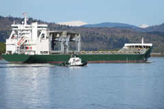Cargo ship maritime transportation. A cargo ship in transit on the Columbia river with a tug boat by his side royalty free stock image