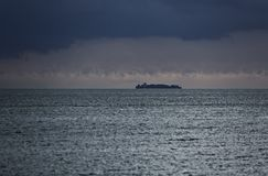 Industrial. A cargo ship in the middle of the sea is wide with a view of the evening Stock Images