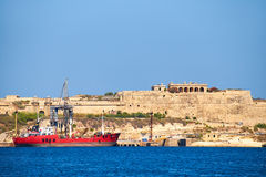 The cargo ship moored at the pier near the Fort Ricasoli, Kalkar Stock Photography