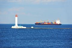 Cargo ship near lighthouse Stock Images