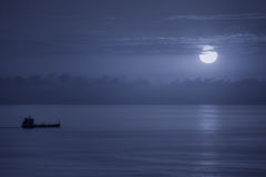 Cargo ship at night with moonlight Stock Image