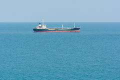 Cargo ship in ocean blue water Royalty Free Stock Photos
