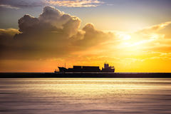 Cargo ship in the ocean at sunset sky Stock Photography