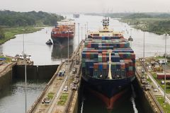 Cargo Ship in Panama Canal. Several freighters, assisted by tugboats, are entering the Panama Canal at Gatun Locks on the Atlantic side. These container ships Royalty Free Stock Image
