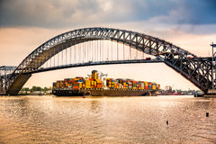 Cargo ship passes under Bayonne Bridge, NJ Stock Image