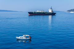 Cargo ship passing a small boat on the Adriatic sea Stock Photo