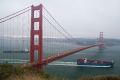 Cargo Ship Passing Underneath Golden Gate Bridge Royalty Free Stock Photos