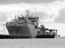 Cargo ship in port. Black and white image of a massive cargo ship being unloaded Royalty Free Stock Photo