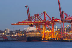 Cargo Ship and Port. A cargo ship is docked and unloading cargo Stock Images