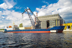Cargo ship in the port and cargo crane on the pier. Cargo ship in the port and cargo crane on the pier royalty free stock photography