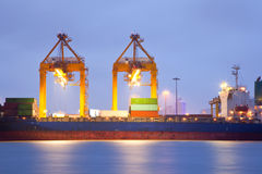 Cargo ship in port at dusk Stock Images