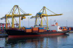 Cargo Ship in Port Loading Containers. Gantry cranes lifting containers onto sea-going cargo ship Royalty Free Stock Photography