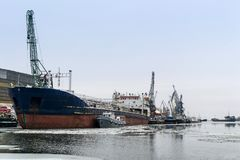 Cargo ship in the port near the pier in winter among the ice stock photography