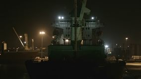 Cargo Ship in Port at Night. Industrial backgrounds - cargo ship moored in port at night. Calm scene of very dark night in commercial harbour stock footage