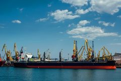 Cargo ship is in port. Cargo ship stands in an industrial port on a sunny day Royalty Free Stock Photos
