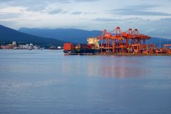 Cargo ship in port in Vancouver, British Columbia, Canada. A cargo ship in Vancouver's harbour at sunset being either loaded or unloaded with cranes Royalty Free Stock Image