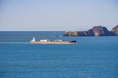 Cargo ship preparing to enter San Francisco bay; in the background Point Bonita Lighthouse, California royalty free stock photo