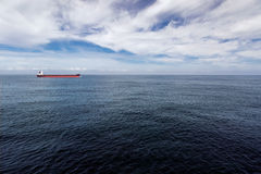 Cargo ship is proceeding through the sea. Red and black cargo ship is proceeding through the sea Royalty Free Stock Images