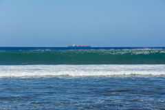Cargo ship riding a wave Stock Images