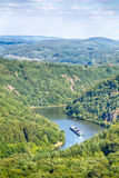 Cargo Ship on a River in Germany. A cargo ship sails through the Saar river in Germany between wooded hills near the city of Mettlach Stock Image