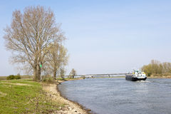 Cargo ship on river in rural scenery Royalty Free Stock Photo