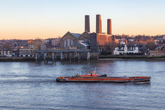 Cargo ship on the River Thames at the Greenwich power station. Evening shot in winter with lovely light and shows a barge pulling an aggregate carrier up the stock photos