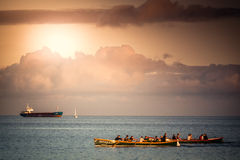 Cargo ship and rowing boats Royalty Free Stock Photo