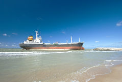 Cargo ship run aground on rocky shore Stock Images