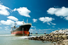 Cargo ship run aground on rocky shore Stock Photo