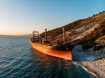 Cargo ship run aground at sea coastline. Shipwreck accident of nautical vessel after huge sea storm, aerial view. Cargo ship run aground at sea coastline near stock images