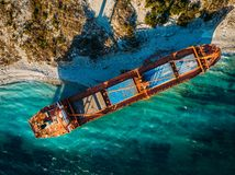 Cargo ship run aground at sea coastline. Shipwreck accident of nautical vessel after huge sea storm, aerial view. Cargo ship run aground at sea coastline near royalty free stock photos