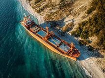 Cargo ship run aground at sea coastline. Shipwreck accident of nautical vessel after huge sea storm, aerial view. Cargo ship run aground at sea coastline near stock image