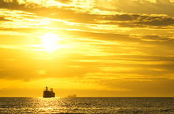 Cargo ship sailing away Royalty Free Stock Photos