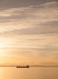 Cargo ship sailing past distant islands Stock Photography