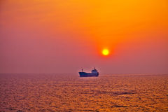 Cargo ship sailing sunrise Royalty Free Stock Photos