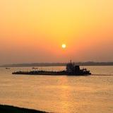 Cargo ship sailing at sunset Stock Image
