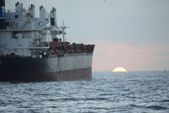 Cargo Ship sailing into the sunset Royalty Free Stock Images