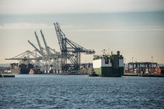 Cargo ship sailing to commercial port with cranes Royalty Free Stock Photography